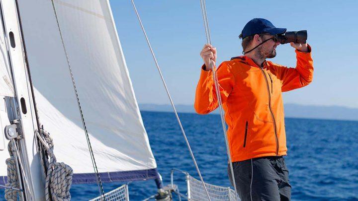 Капитан с биноклем на яхте